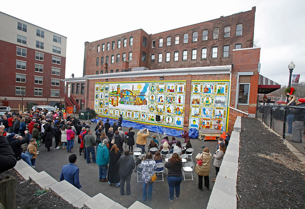MIKE SPRINGER/Staff photo A crowd watches the unveiling Sunday of Alexander Golob's mural depticting Haverhill's immigrant heritage on the side of the Garibaldi Club building at 86 Washington Street in downtown Haverhill. 12/16/2018