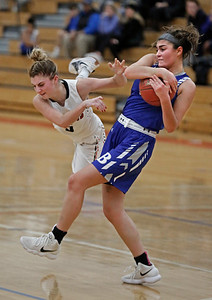 MIKE SPRINGER/Staff photo Bedford's Danielle Arnold, right, wrests the ball from Norah Connors of North Andover during varsity basketball play Sunday at Tewksbury Memorial High School. 12/16/2018