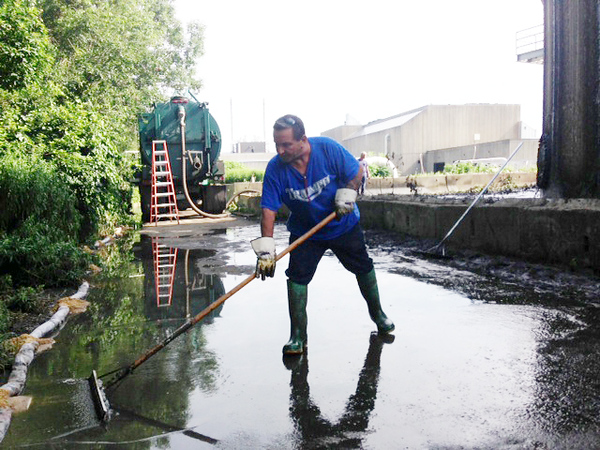 "William Ferrier, a plant operator at the Greater Lawrence Sanitary District, said the ongoing spills at the treatment tanks are ""part of the nature of the beast"" because of the way the tanks are designed. He uses a Squeegee to push waste back from a wetlands beside the plant."