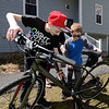RYAN HUTTON/ Staff photo<br /> Liam Mullaly, 12, left, shows his brother Connor, 10, right,  how the gears of his bike shift outside their Windham home. Liam is participating in a fundraising bike ride for his brother, who is battling Duchenne muscular dystrophy.