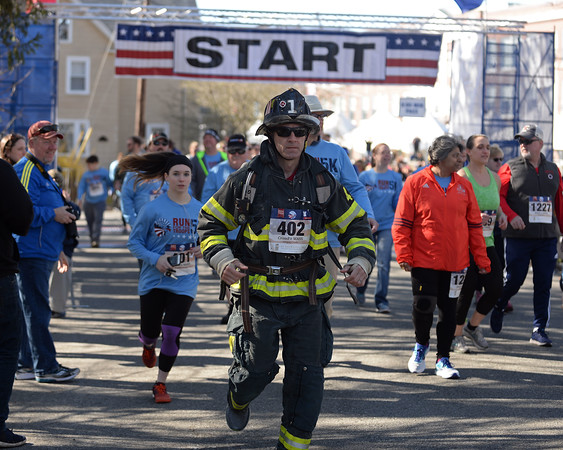 RYAN HUTTON/ Staff photo<br /> Wearing full firefighter turnout gear, Gregory Cinelli, of Haverhill, runs down the first stretch of the Run for the Troops 5K on Whittier Street in Andover on Sunday morning.