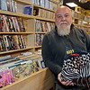 """RYAN HUTTON/ Staff photo<br /> Comically Speaking owner Patrick Jammal stands in his shop's vinyl records aisle with a copy of his favorite KISS album """"Animilize"""" which recently came into the shop."""