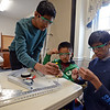 RYAN HUTTON/ Staff photo<br /> From left, Arjun Chandra, 13, Aaron Han, 11, and Aadi Trivedi, 13, work on the frame of a wheeled robot at the Derive Robotics class taught by Andover High School seniors at the Faith Lutheran Church in Andover.