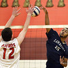 CARL RUSSO/Staff photo. Lawrence's Andre Wilson spikes the ball over the net. Lawrence high defeated Pinkerton Academy in boys volleyball action Saturday afternoon. 4/28/2018