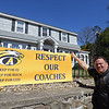 RYAN HUTTON/ Staff photo<br /> Dan Gillette stands next to the banner he has hung at his Moraine Street home voicing support for three Andover High coaches; EJ Perry, Christopher Kuchar and David Cudman.