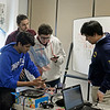 RYAN HUTTON/ Staff photo<br /> From left, Andover High School seniors Aum Trived, 18, Aurash Bozorgzaeeh, 18, Joshua Krinsky, 17, and Alex Yang, 17, try to get one of the smart-phone powered robots working at the Derive Robotics class they teach at the Faith Lutheran Church in Andover.