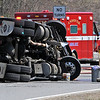 TIM JEAN/Staff photo<br />   <br /> An Andover firefighter watches fuel drill into a bucket as State police investigate the scene where a tractor-trailer rolled over on the ramp from Interstate 495 North to Interstate 93 South. The truck spilled fuel as well as watermelons onto the highway.  4/28/18