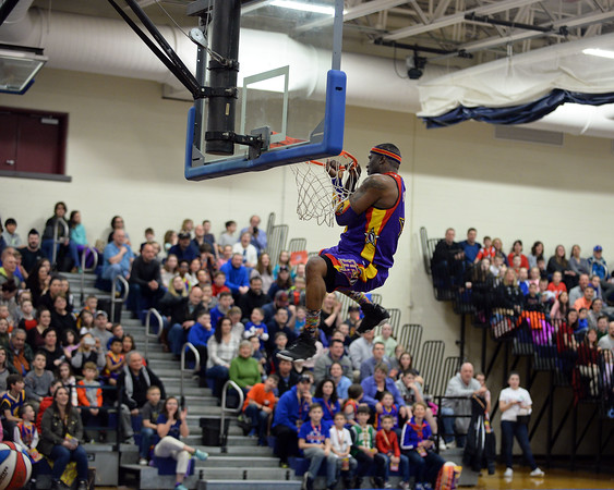 """RYAN HUTTON/ Staff photo<br /> Leon """"Space Jam"""" Sewell hangs from the rim after dunking in the Londonderry High School gym during the Harlem Wizards show on Monday night."""
