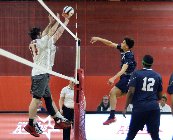 CARL RUSSO/Staff photo. Lawrence's Miguel Jackson spikes the ball over the net. Lawrence high defeated Pinkerton Academy in boys volleyball action Saturday afternoon. 4/28/2018