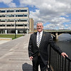 RYAN HUTTON/ Staff photo<br /> Pentucket Bank CEO Scott Cote stands on the walk by the Merrimack River with the bank's new offices at Harbor Place in the background.