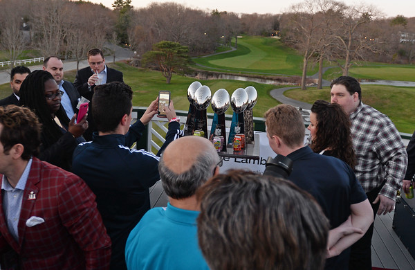 RYAN HUTTON/ Staff photo<br /> Fans take pictures of the New England Patriots' five Lombardi trophies at the Stellato Sports Draft Party at the Ferncroft Country Club.
