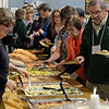 RYAN HUTTON/ Staff photo<br /> Former and current Derry Village Elementary School faculty and staff work their way through the buffet in the school's gymnasium during the school's 50th anniversary reception on Thursday night.