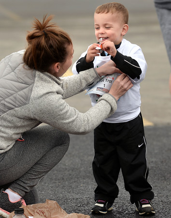 CARL RUSSO/Staff photo. Meghan Richard of Lowell pins her nephew's bib on, Roderick Lefort, 3, of Litchfield as he enjoys a piece of candy before the Tot Trot. Applewood Learning Center, a non-profit childcare center in the Derry/Londonderry area, held their annual Tot Trot and 5K race fundraiser at the Moose Hill School in Londonderry Saturday morning. 4/28/2018