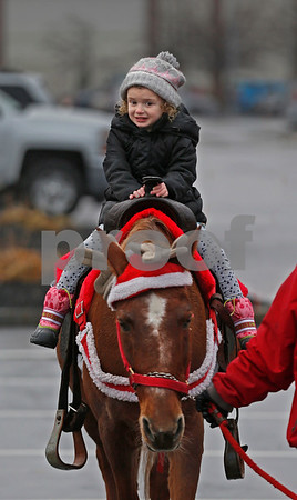 MIKE SPRINGER/Staff photo<br /> Four-year-old Bryn Couture puts on a brave face as she rides a pony during the Methuen tree-lighting festivities Sunday at the Loop shopping mall.<br /> 12/02/2018