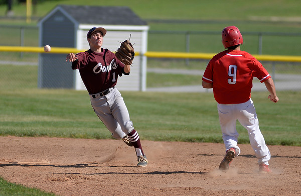 RYAN HUTTON/ Staff photo<br /> Timberlane's Christian Alaire fires the ball to first after making the out on Pinkerton's David Currier during the third inning of Thursday's game at Timberlane. Pinkerton won 3-1 after 11 innings.