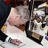 CARL RUSSO/Staff photo. STEPPING OUT:  Governor Charlie Baker makes a bid for one of the auction items-autographed photo of Bruins Brad Marchand before giving his speech.                                                                                     The Greater Lawrence Family Health Center's annual making a Difference Gala was held Thursday night, April 12 at the Andover Country Club. Massachusetts Governor, Charlie Baker was the keynote speaker. Lawrence Mayor, Daniel Rivera was this year's recipient of the Making A Difference award for his work on opioids and the homeless. 4/12/2018