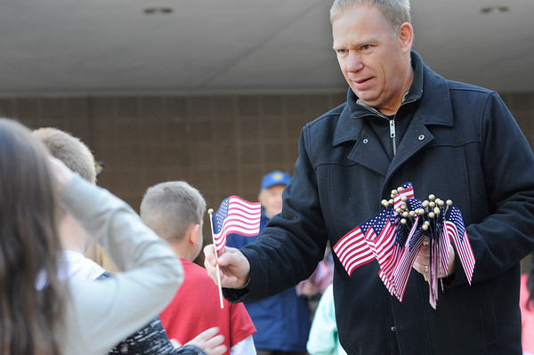 TIM JEAN/Staff photo<br /> <br /> Sean Devan, of the Exchange Club of Lawrence passes out flags to students during the Salute to Veterans program at Pvt. Albert E. Thomson Elementary School. The school is named in honor of Pvt. Albert E. Thomson, who was killed in World War I on Nov. 9, 1918, 100 years ago this day.  11/9/18