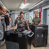 AMANDA SABGA/Staff photo<br /> <br /> City Councilors Ana Levy, center, and Pavel Payano, left, react aa they compare new voting machines to old ones as they are exchanged at Lawrence City Hall. <br /> <br /> 8/1/19
