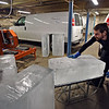 RYAN HUTTON/ Staff photo<br /> Lars-Erik Miller moves a 375 pound ice block toward a modified lumber saw at the Brilliant Ice Sculpture shop in Lawrence on Thursday.