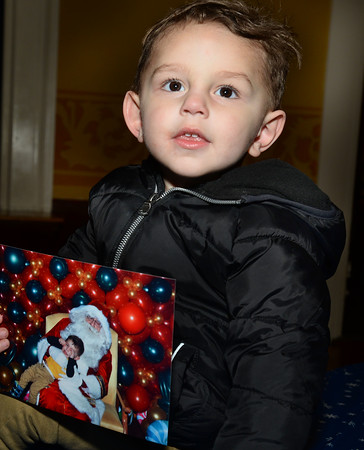 CARL RUSSO/Staff photo. Blake Chaves, 2 who was not happy to have his photo taken with Santa, is happy to pose with the photo. Andover held their annual Holiday Happenings downtown and at the town park Friday night. 12/13/2019
