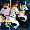 CARL RUSSO/Staff photo. Connie Mamis, 5 and her brother, Brody, 2 ride the merry-go-round. Andover held their annual Holiday Happenings downtown and at the town park Friday night. 12/13/2019