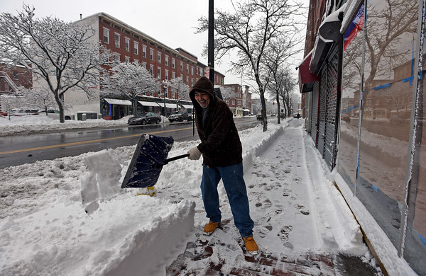 RYAN HUTTON/ Staff photo<br /> Robert Mendez shovels the sidewalk on Essex Street in Lawrence durning Monday morning's storm.