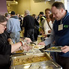 TIM JEAN/Staff photo <br /> <br /> Mary Guerrero, left, of Cafe Azteca gives a a sample of authentic Mexican cuisine to Brad Buschur, Project Director at Groundwork Lawrence during the Lawrence Partnership annual meeting held at IndusPad.     12/18/19