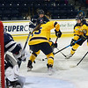 CARL RUSSO/Staff photo. Merrimack's Dani Castino, right and Allison Reeb fight for the puck in front ofUNH's goalie, Ava Boutilier. The Merrimack College Warriors were defeated by the University of New Hampshire Wildcats in women's hockey action Friday night.12/06/2019