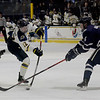 TIM JEAN/Staff photo <br /> <br /> Merrimack's Jordan Seyfert shoots the puck past UNH defensemen Max Gildon during the first period of a Mens Ice Hockey game at Merrimack College.    12/7/19