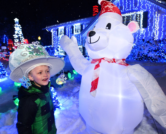 CARL RUSSO/Staff photo. Luca Sanzo, 5 looks at one of many (over 100) inflatables in front of his house. <br /> <br /> Kendra and Keith Sanzo of Pelham and their children; Kaylee Boutin, 16; Aiden Sanzo, 14 and Zachary Boutin, 18. Standing in the front; Christian Sanzo, 11 and Luca Sanzo, 5. Over the past 15 years Kendra and Keith Sanzo of Pelham and their children have put in thousands of hours to set up their front yard Christmas lights display. This year they doubled the effort which now includes 107 inflatable decorations, dozens of figurines and over 100,000 lights. Lights on every day 2:30-11pm. 12/02/2019