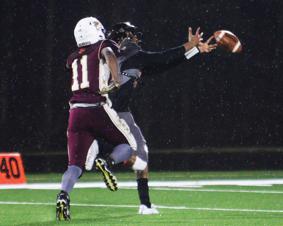 CARL RUSSO/Staff photo. The wet football and long pass is just out of reach for the hands of Reggie Christopher Tineo as Whittier's Yuki Efosa keeps up with him. Whittier Wildcats defeated the Greater Lawrence Reggies in Thanksgiving Eve football action. 11/27/2019