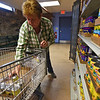 RYAN HUTTON/ Staff photo<br /> Marlene Linehan stocks the shelves at the Liz Murphy Open Hand Food Pantry in Haverhill on Tuesday morning.
