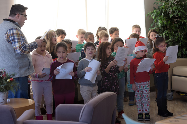 TIM JEAN/Staff photo <br /> <br /> Chris Rossi, left, Lead Teacher and his students from Hill View Montessori Public Charter School sing holiday songs to patients and staff at Whittier Rehabilitation Hospital.   12/20/19