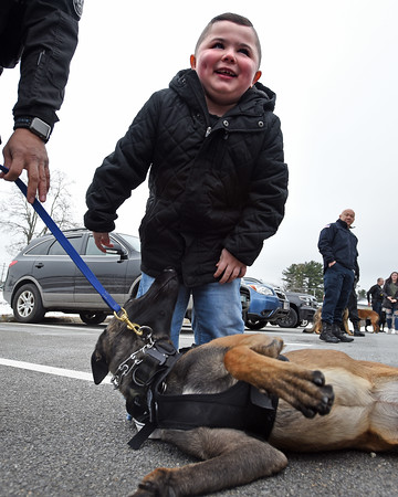 RYAN HUTTON/ Staff photo<br /> Aiden Moore, 8, smiles as Lawrence Police K-9 Magnus offers up his belly for rubs outside the Derry Police Department on Friday morning.Nearly a dozen police dogs and their handlers showed up to help present Aiden's family with a handicap accessible van which they will need as his Duchenne Muscular Dystrophy worsens.