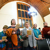 CARL RUSSO/Staff photo.  With a 12 glass panel historical Searles window as their backdrop, Hannah Giegerich of Derry N.H. and her sons, Austin, 9, left and August, 10 enjoy singing carols along with Sienna Sovereign, far right, 15 and her sister Erica Sovereign, 14 of Windham, N.H. They were attending the Christmas Eve Carol Sing, sponsored by the Heritage Baptist Church in Windham and held at the historic Searles School and Chapel. All are members of Heritage Baptist Church.       <br /> <br /> Around 125 members of the church and guest enjoyed singing or just listening to the traditional Christmas carols. 12/24/2019