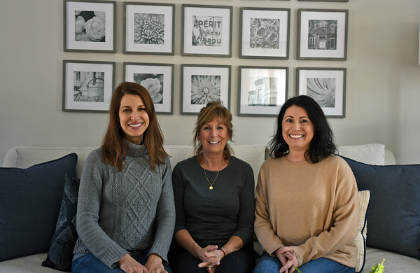 RYAN HUTTON/ Staff photo<br /> Homeowner Kate Duff, center, sits with Gray Oak Studio owners Leah Hook, left, and Sonia Brady, right, in her newly renovated and redesigned living room.