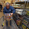 RYAN HUTTON/ Staff photo<br /> Bob Dilando fills up a cart full of canned food while stocking the shelves at the Liz Murphy Open Hand Food Pantry in Haverhill on Tuesday morning.
