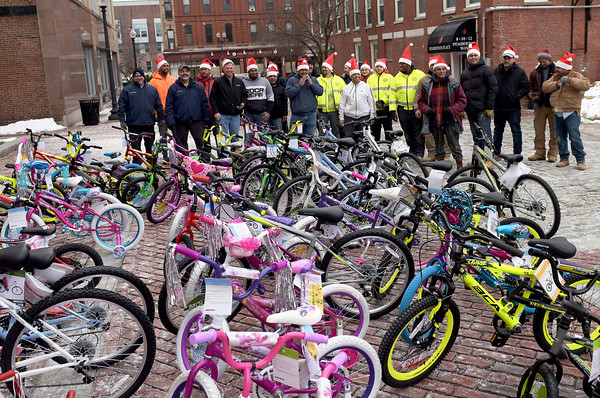 TIM JEAN/Staff photo <br /> <br /> Construction workers from Brady Sullivan Properties, who are building apartments in the Pacific Mills Lofts sings holiday songs after they brought 50 bicycles to be donated to Lawrence City Hall.     12/13/19