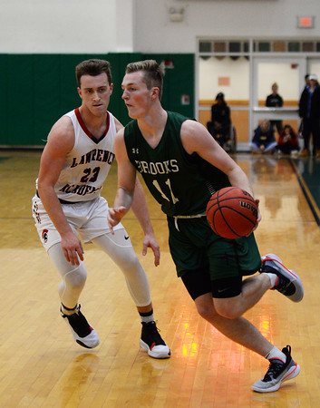 CARL RUSSO/staff photo. Brooks' George Smith of Salem NH drives to the hoop against Lawrence Academy's captain, Richard Jordan of Lawrence.  Lawrence Academy at Brooks School in boys basketball action. 12/11/2019