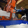 RYAN HUTTON/ Staff photo<br /> Lars-Erik Miller, right, cuts an inch or two off of a 300 pound ice block in the Brilliant Ice Sculpture shop in Lawrence while owner Don Chapelle looks on, left.