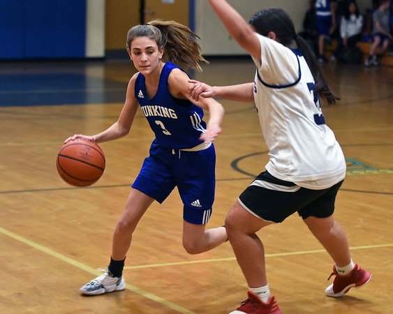 RYAN HUTTON/ Staff photo<br /> Hunking Middle School's Sam Guertin tries to drive around Nettle Middle School's Lexi Cortes during Thursday afternoon's game at Nettle.