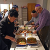 RYAN HUTTON/ Staff photo<br /> Members of Congregation Beth Israel in Andover serve themselves food at the start of the Shabbat celebration on the first night of Hanukkah on Friday.