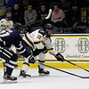 TIM JEAN/Staff photo <br /> <br /> Merrimack's Griff Jeszka carries the puck past UNH defensemen Anthony Wyse during the first period of a Mens Ice Hockey game at Merrimack College.    12/7/19