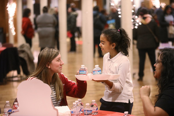 MIKE SPRINGER/Staff photo<br /> Solymar Lopez, right, a fourth-grader at Frost Elementary School, serves water to Raychel Pennisi, an eighth-grader at Hunking Middle School in Haverhill, during a student art show Thursday evening at Everett Mills in Lawrence.<br /> 12/5/2019