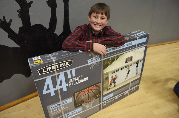 TIM JEAN/Staff photo <br /> <br /> Josiah Mendez, 10, shows off the basketball backboard set he won in a raffle during Haverhill's Boys & Girls Club annual Christmas party.     12/13/19