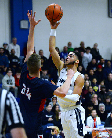 CARL RUSSO/Staff photo. Lawrence's Angel Herrera sails over Central's Anthony Traficante for the basket. Lawrence high defeated Central Catholic 55-51 in the 7th. Annual Commonwealth Motors Christmas Classic basketball tournament. 12/27/2019