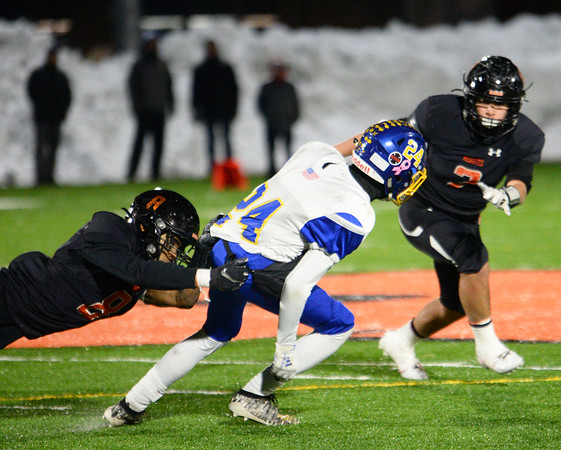 CARL RUSSO/Staff photo. Greater Lawrence's Franklyn Espinal dives from behind as Maleek Dejesus gets ready to tackle Assabet Valley runner from the front. Greater Lawrence Tech. defeated Assabet Valley 36-26 in State Vocational Bowl Thursday night. 12/05/2019