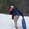 RYAN HUTTON/ Staff photo<br /> Brandon Brown, of Windham, carries his daughter Madison, 3, up the sledding hill at Alexander Carr Park in Derry on Monday.