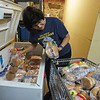 RYAN HUTTON/ Staff photo<br /> Jackie Paynter fills up a cart from a freezer to stock the shelves at the Liz Murphy Open Hand Food Pantry in Haverhill on Tuesday morning.