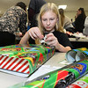 CARL RUSSO/Staff photo. Jorie McIrvin, 13 of Haverhill participated in the party with her father, Matt McIrvin. <br /> <br /> Foster Kids of the Merrimack Valley, a non-profit organization held its 14th. annual Wrapping Party Thursday night at St. Lucy's Parish in Methuen. Over 150 volunteers participated in wrapping hundreds of gifts for the kids. Eileen and Larry Giordano of Methuen are the founders of Foster Kids of the Merrimack Valley Inc. with Larry as president and Eileen as vice president. 12/12/2019